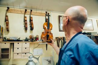 Владимир держит в руках очередную скрипку, которую закончил в этом году. Цена инструмента - около 5000 евро. Фото - Антон Белицкий / МОСЛЕНТА