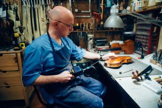 При помощи телевизора (выносной камеры с монитором) Владимир осматривает скрипку изнутри. Фото - Антон Белицкий / МОСЛЕНТА
