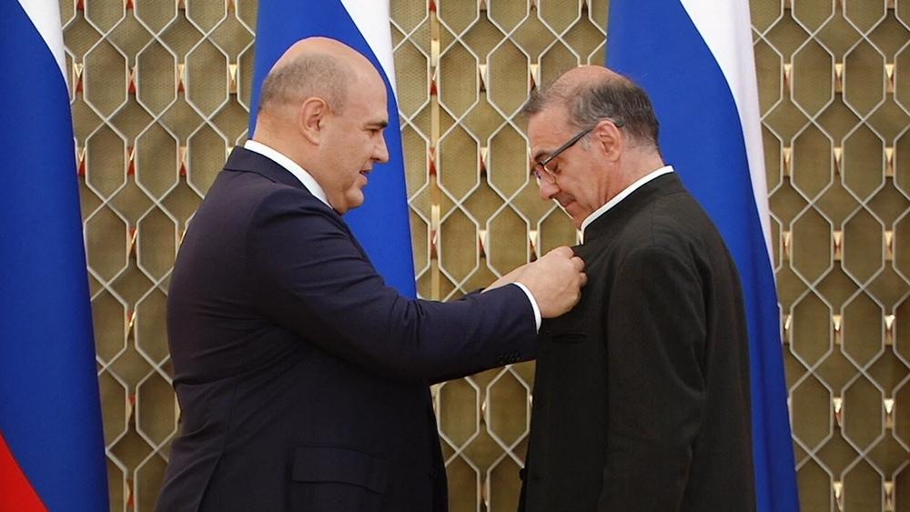 Михаил Мишустин вручает награду Александру Рудину